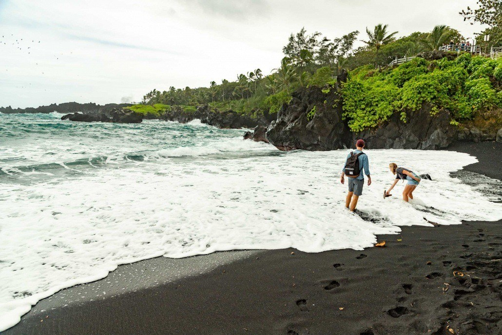 Road to Hana Black Sand Beach Visitors in Surf Waianapanapa Maui