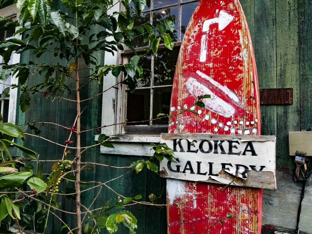 An old gallery sign made from a surf board in Keokea