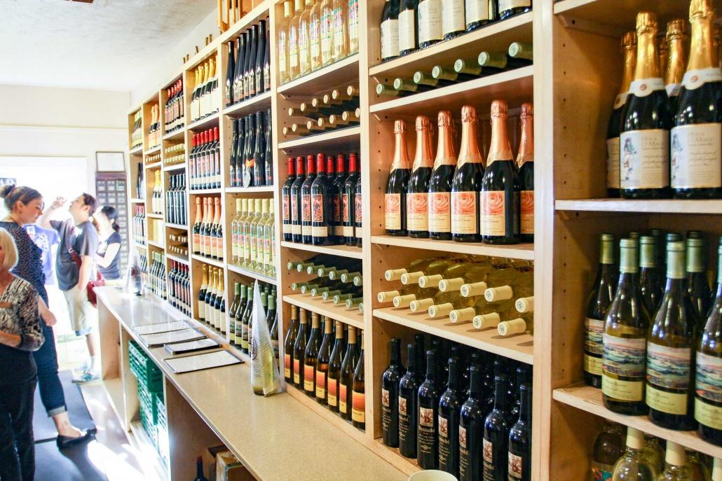 wine bottles line wall at tasting room at Maui Winery